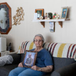 Senior woman holding picture of her husband who has been transferred away