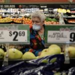 senior woman in mask shopping in grocery store